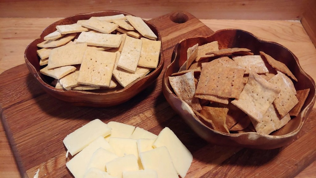 homemade crackers on a cutting board with cheese