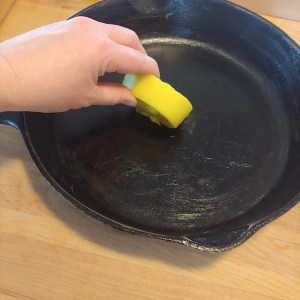 applying a beeswax cast iron conditioning bar to cast iron pan