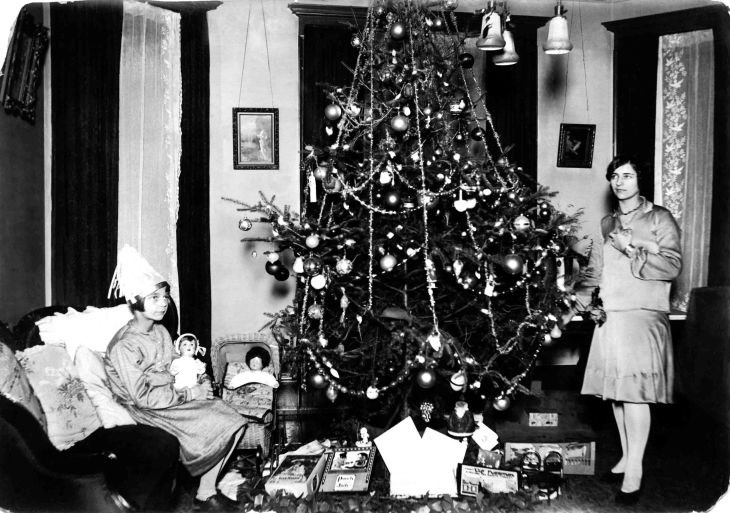 Young Woman And Girl With Gifts By A Christmas Tree 2012.448.1.3