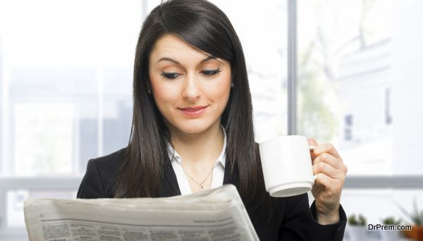 Beautiful woman reading the newspaper while drinking coffee
