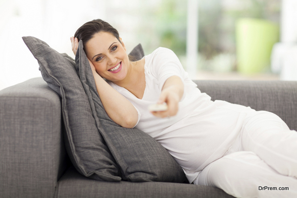 cute pregnant woman watching television