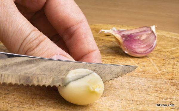 hand slicing garlic cloves on the cutting board with a knife