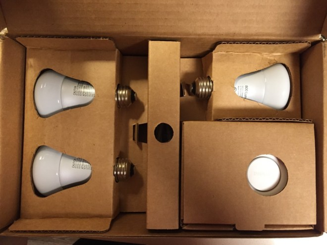 Three Philips Hue bulbs and bridge in their original cardboard shipping box.