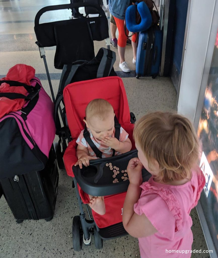 Toddler and baby share a snack on the Joovy Caboose Ultralight Graphite double stroller's snack tray.