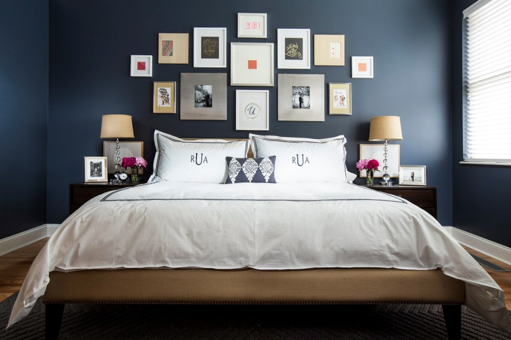 Dark blue bedroom with many frames