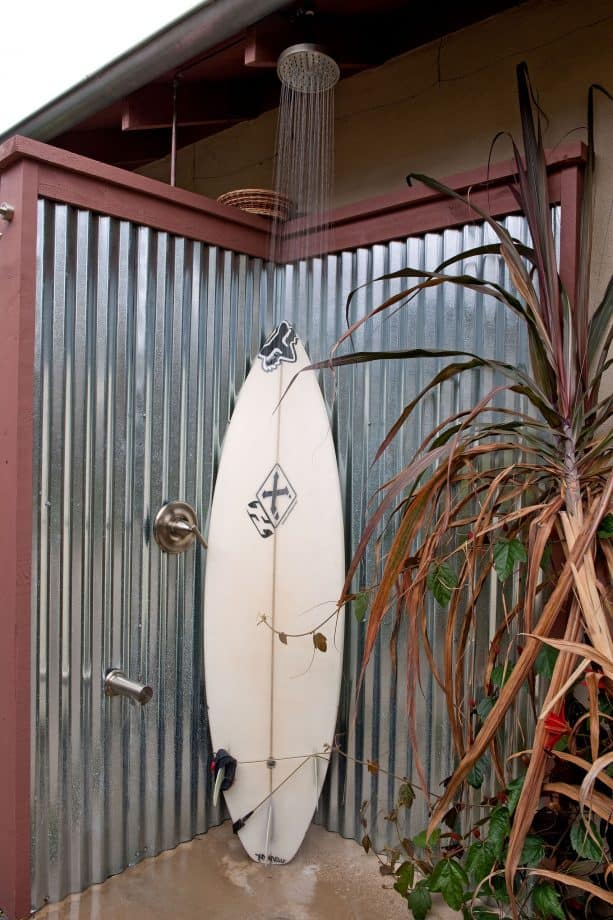 an outdoor shower with corrugated metal fencing as the walls
