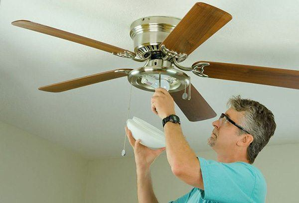DIY Do It Yourself Home Owner Doing Ceiling Fan Repair Work With The Glass  Cover Removed As He Adjusts The Fixture