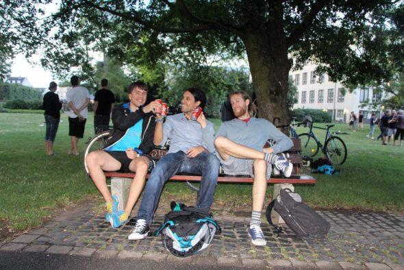 Drei Personen trinken auf Bank Cola-Rum