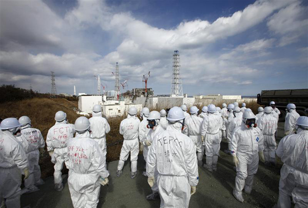 Members of the media wearing protective suits and masks are escorted by TEPCO employees at Tokyo Electric Power Co.'s tsunami-crippled Fukushima Daiichi nuclear power plant