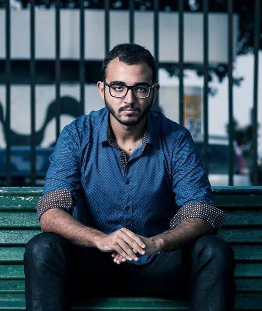 Escritor Raphael Montes sentando em um banco