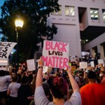 protesters holding signs which say 'Black Lives Matter'