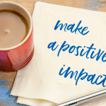 Mug of tea with a napkin next to it with words 'make a positive impact'