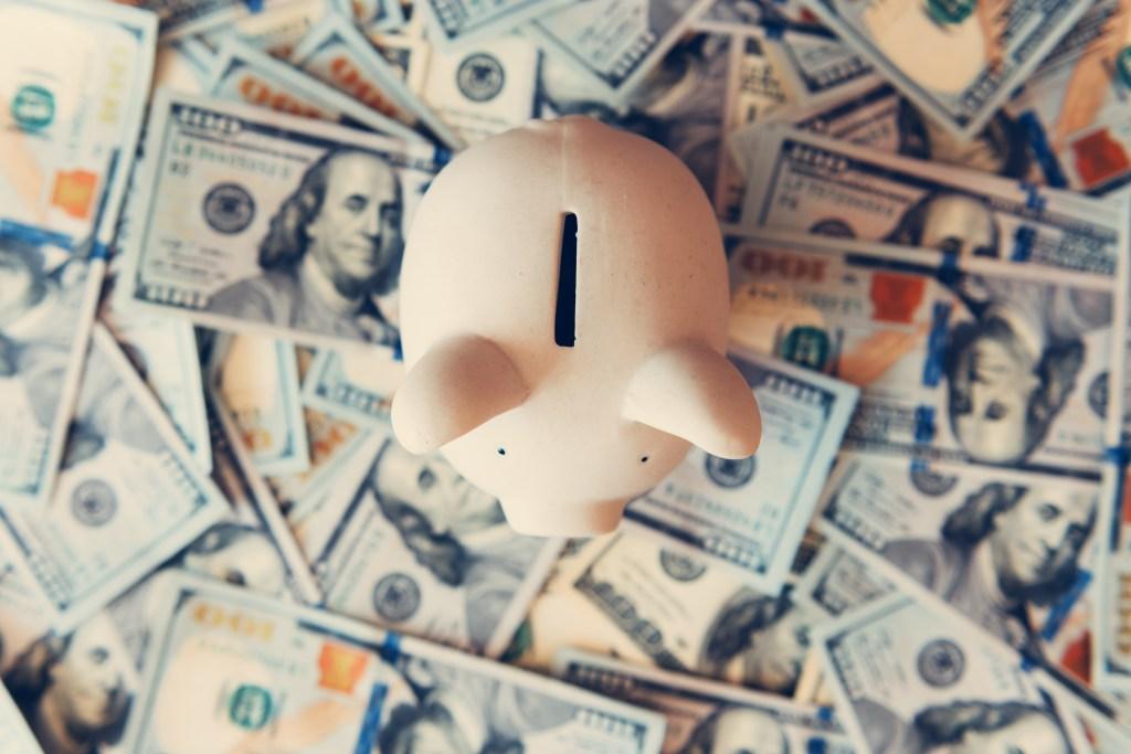 cute piggy bank sitting on assortment of one hundred dollar bills