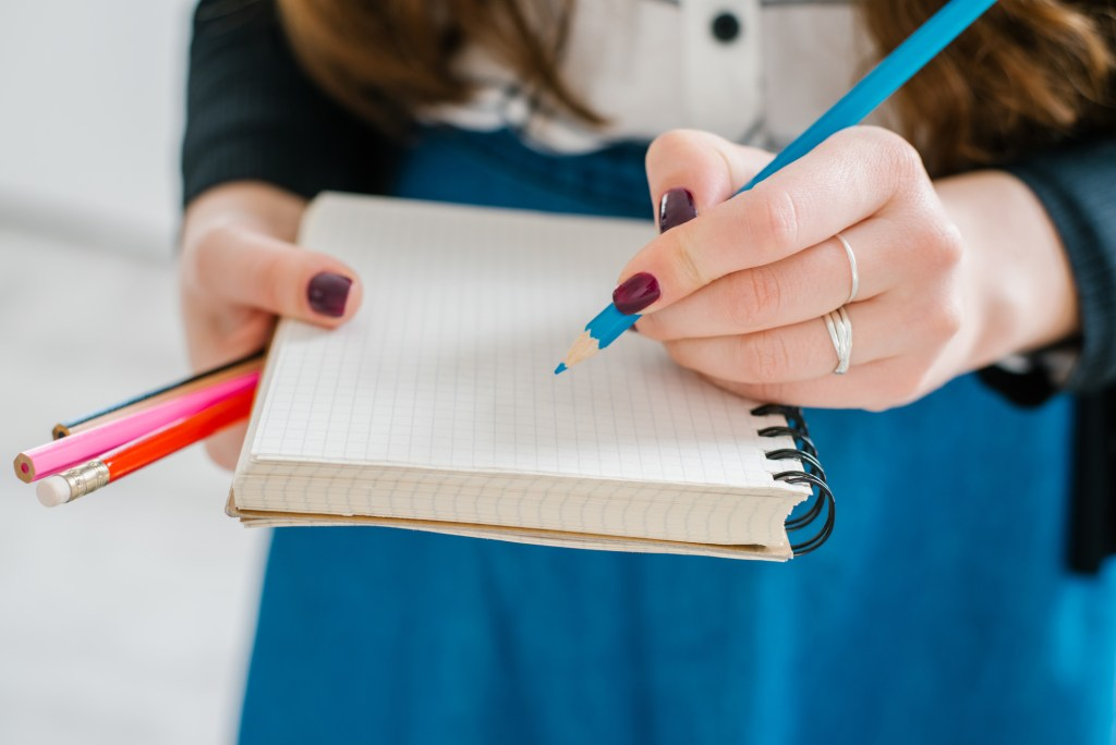 Close up of woman writing with turquoise colored pencil on blank notebook