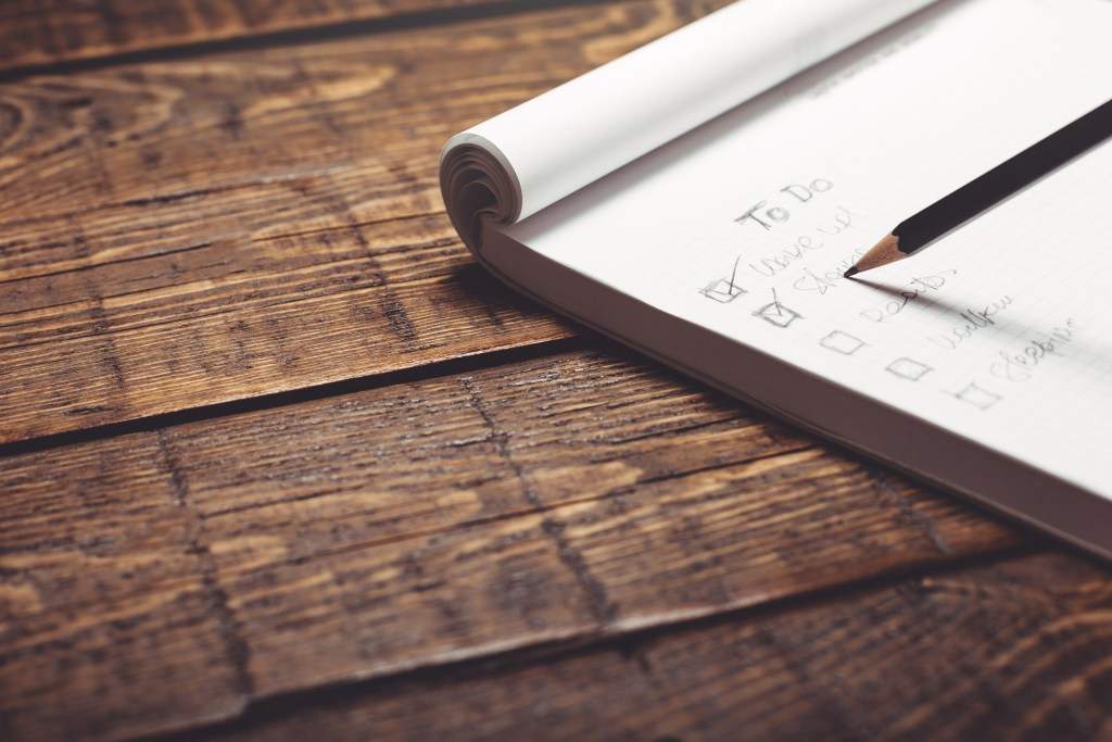 Checking off a to do list with a pencil on a rustic wood desk