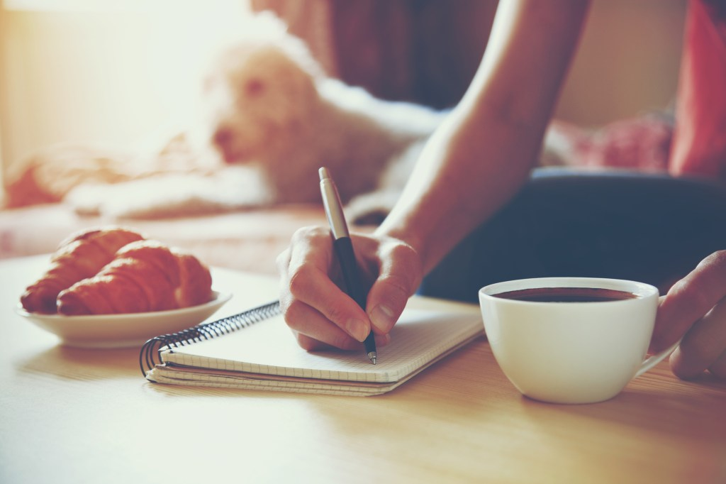 Woman drinking coffee and writing in journal in the morning