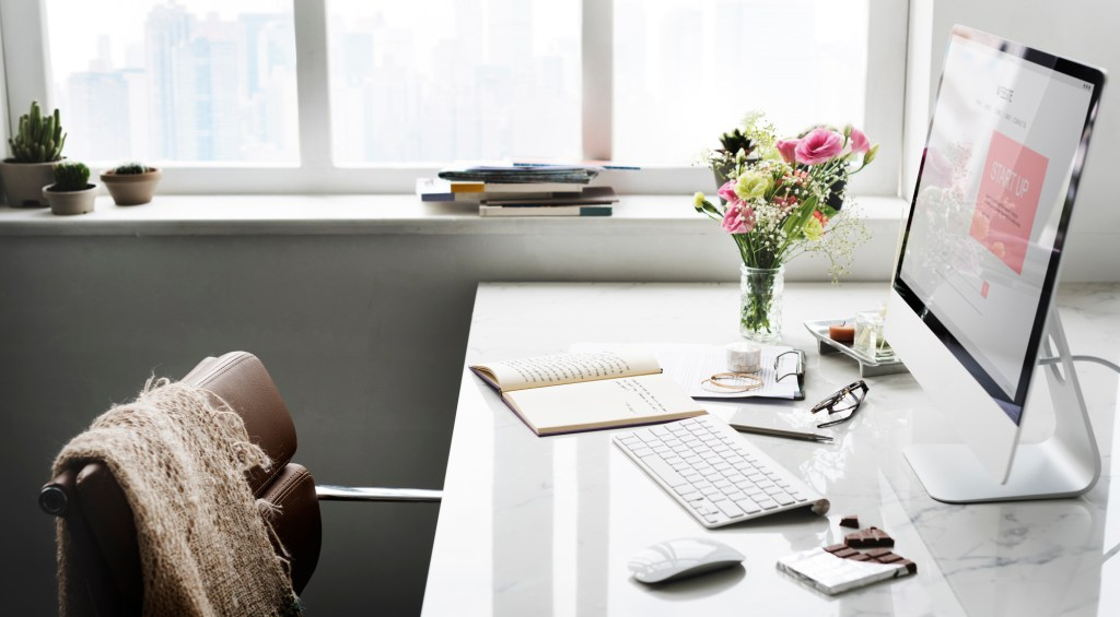 Female desk space with computer, fresh flowers and other modern touches
