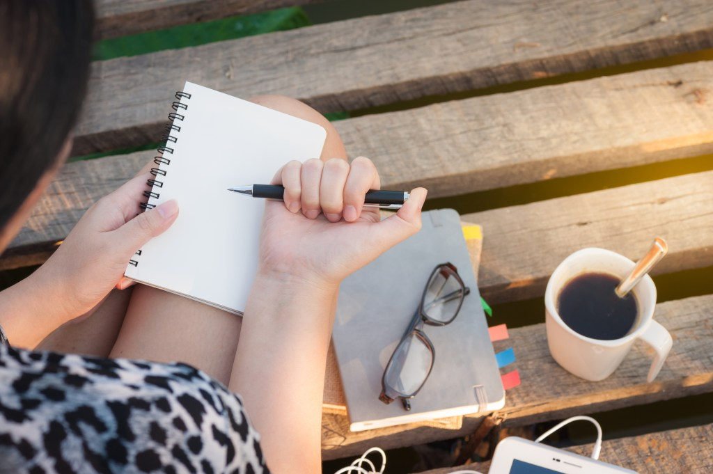 Woman writing in notebook outside
