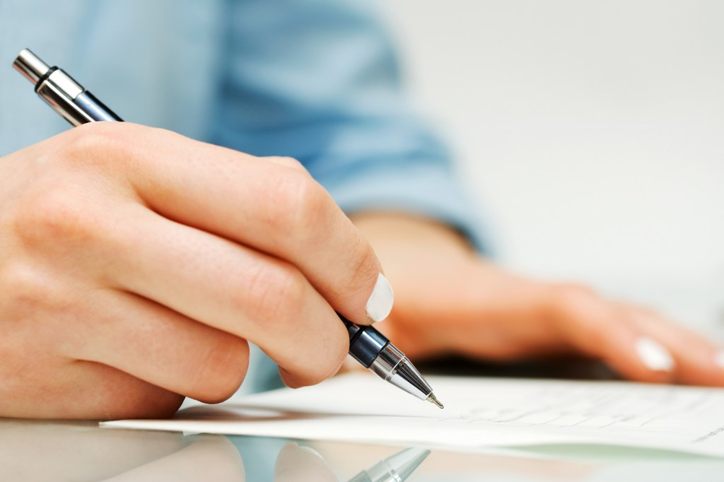 Woman signing piece of paper