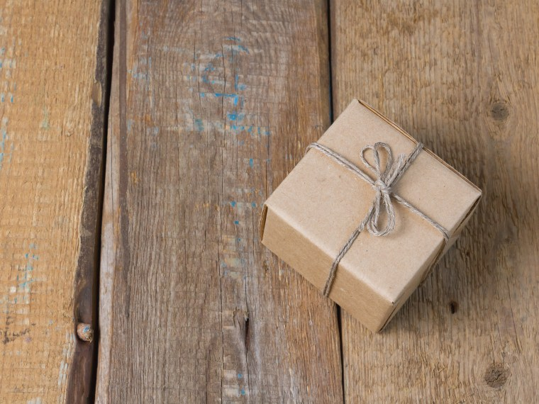Cardboard box tied with a bow and on a rustic wood backdrop