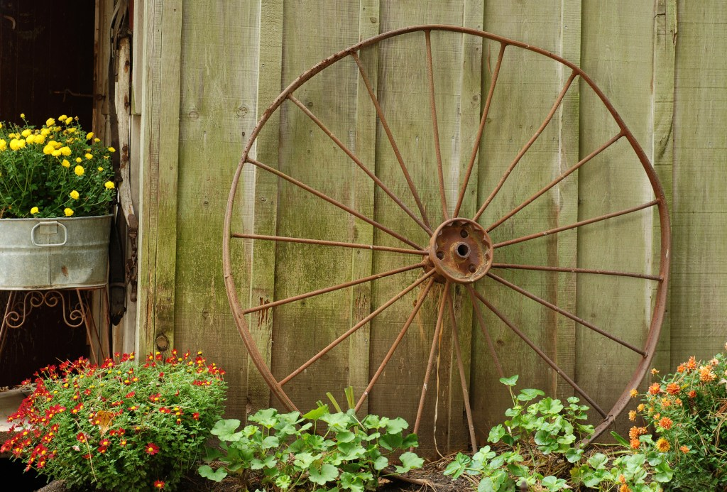 Wagon wheel leaning on wall in garden