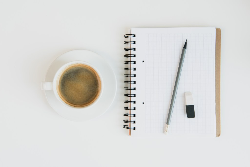 Blank notebook on white surface with coffee cup and pencil