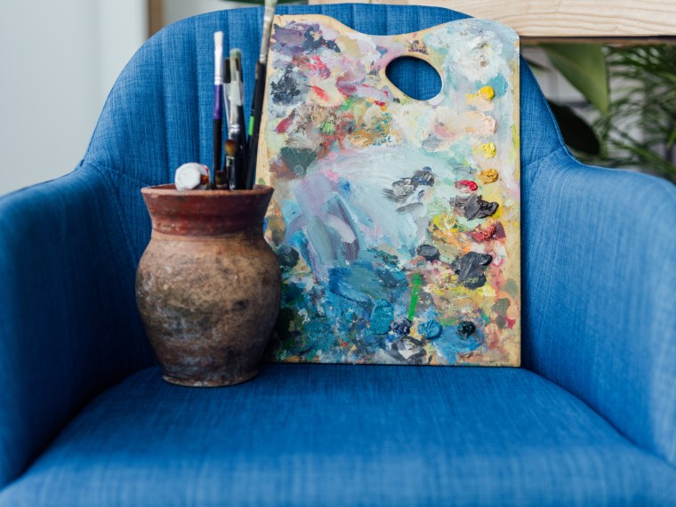 Paint palette and brushes on blue chair