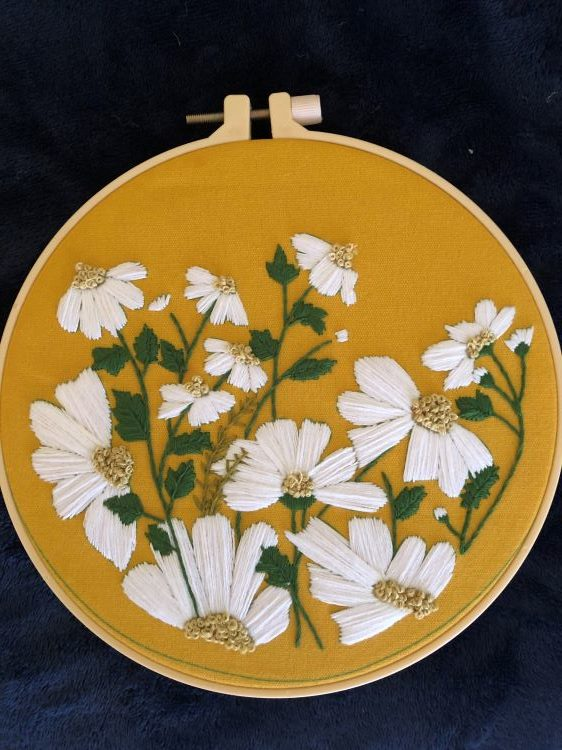 white flowers embroidered on a goldenrod colored fabric