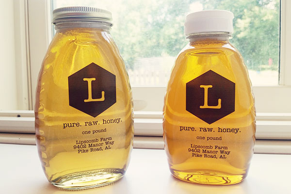 Clear plastic honey labels on two jars of light amber honey.