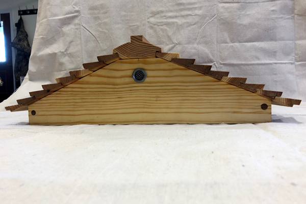 Vent hole in gabled roof of homemade bee hive.