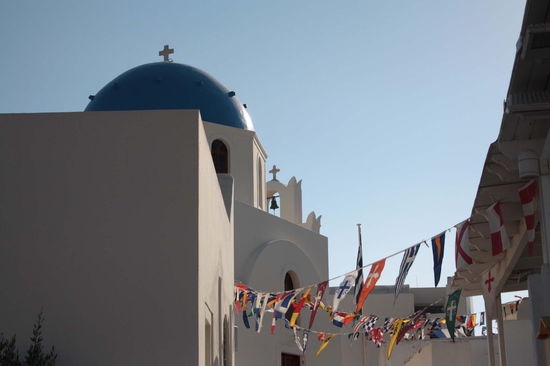 Eglise à coupole bleue à Santorin avec drapeaux