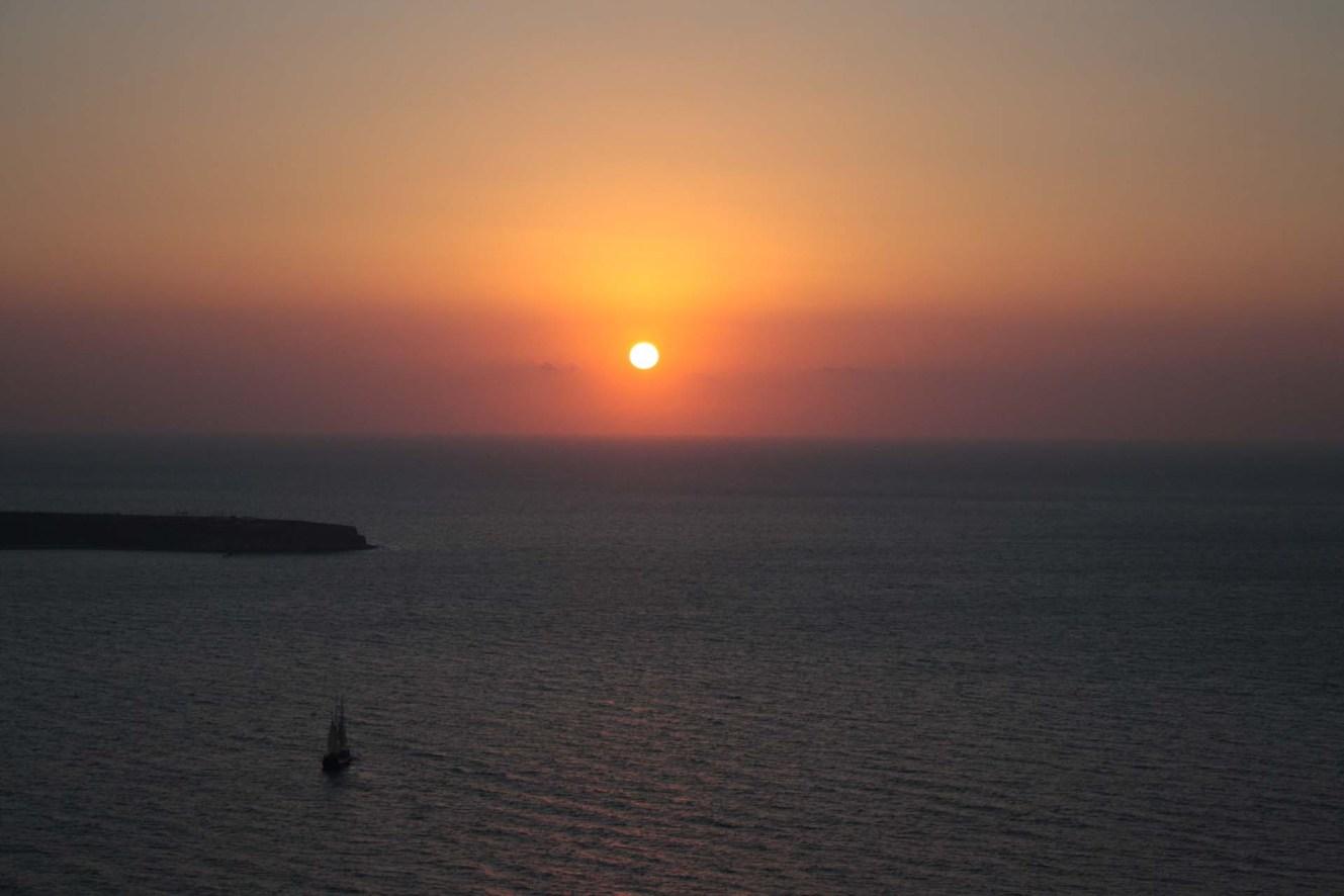 Coucher de soleil sur la mer à Oia Santorin avec bateau