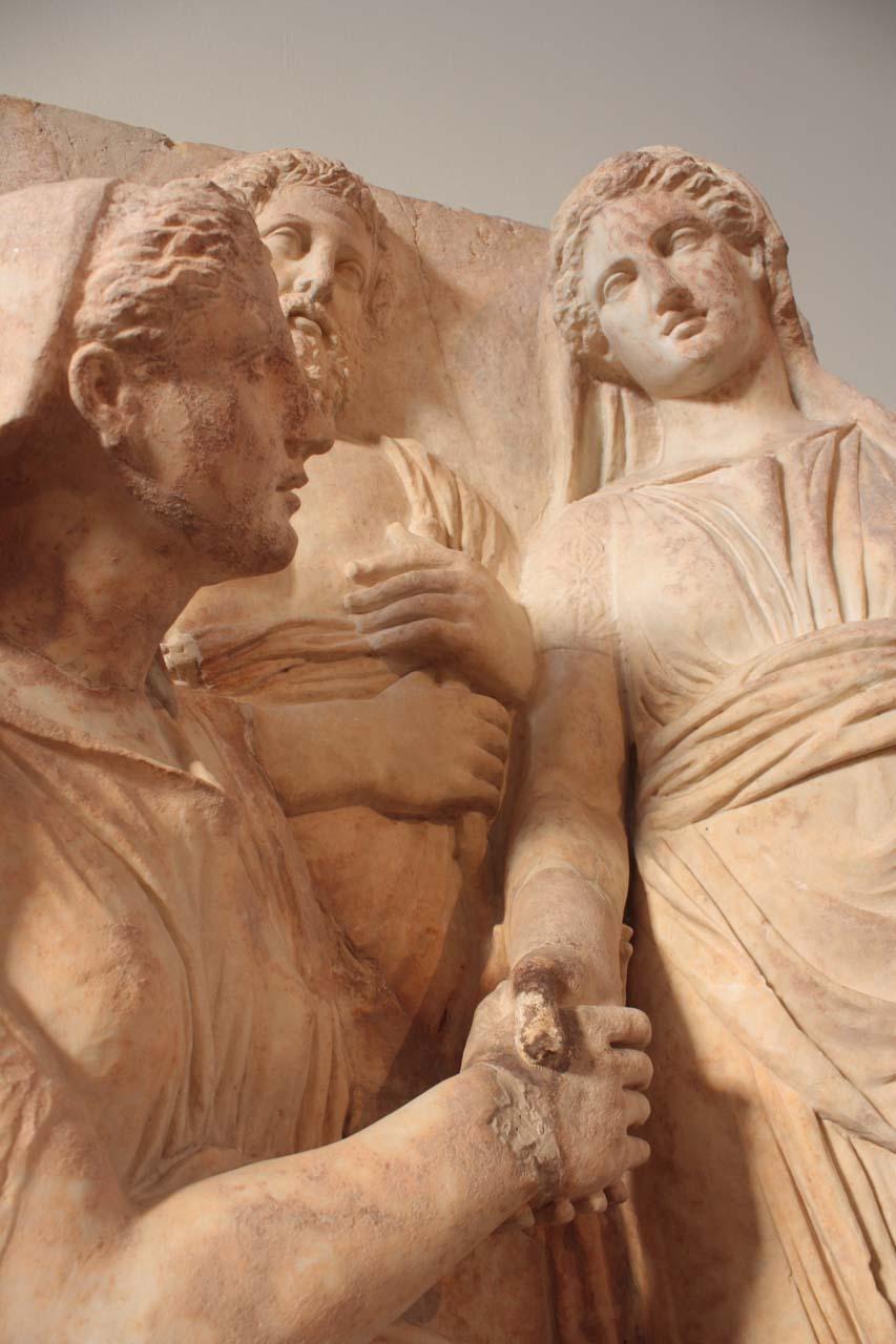 Relief votif dans le Musée National Archéologique d'Athènes avec des femmes qui se serrent la main