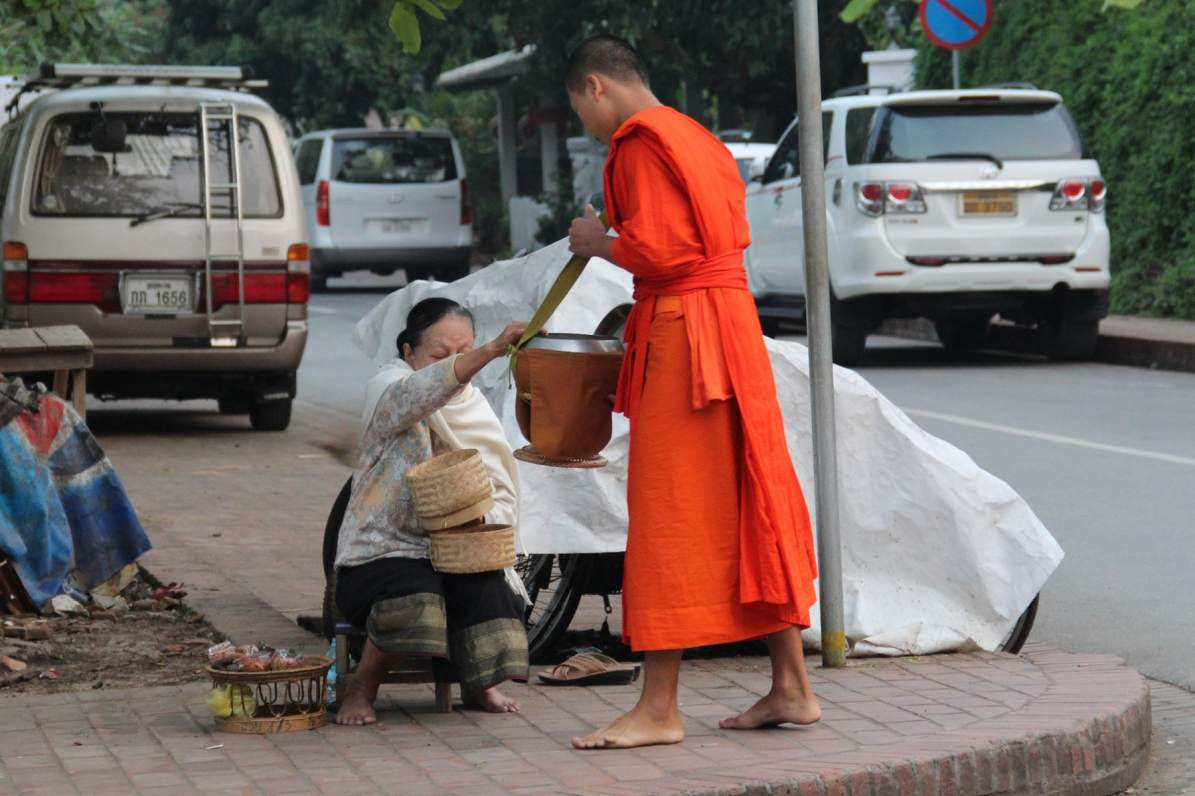 Woman donates rice during alms giving ceremony in Luang Prabang