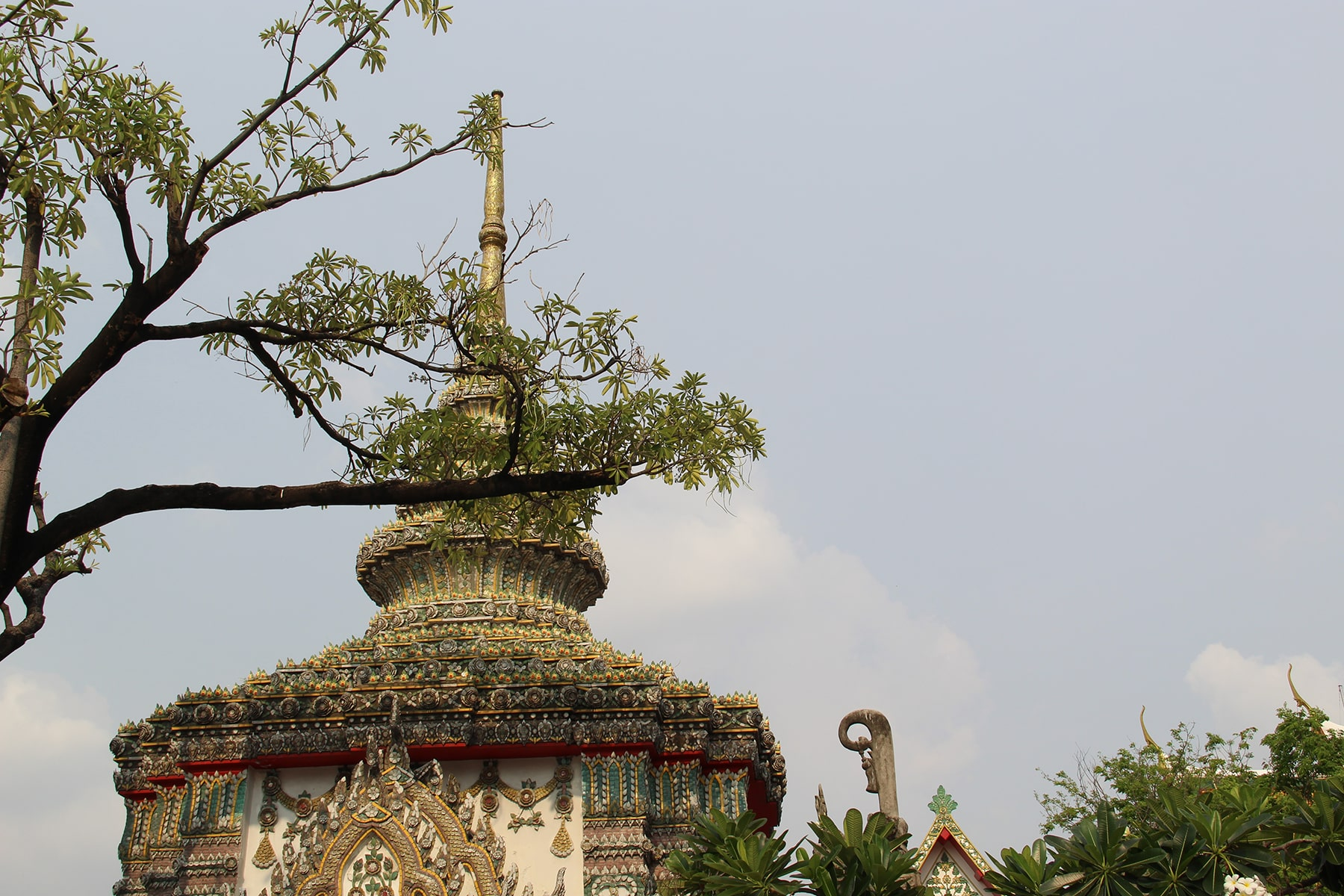 Roof a temple in Wat Pho, Bangkok behind a tree