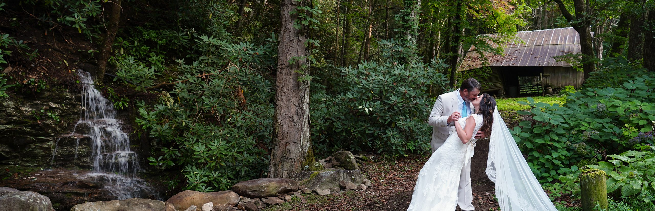 Wedding couple at Smoky Mountain private waterfall near vintage barn