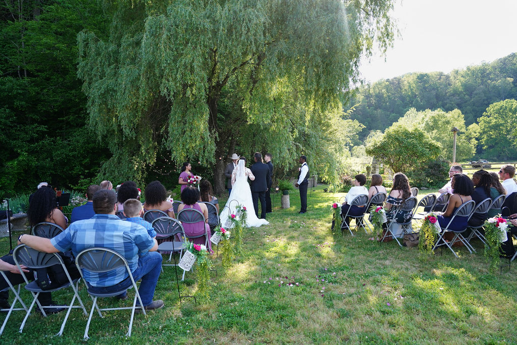 Willow tree wedding ceremony with shepherd hooks and flower vases and guests sitting in gray chairs as the sun goes down