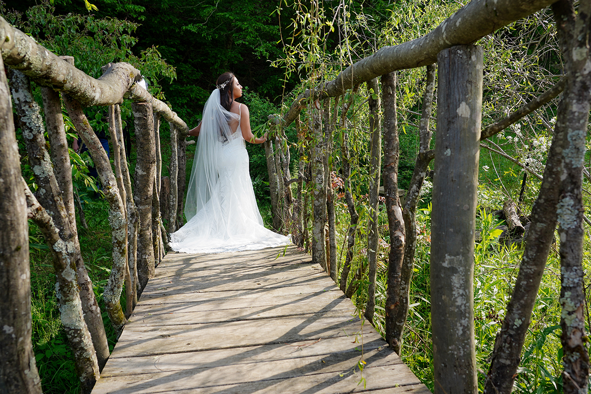 Bride posing on a bridge made of tree limbs that leads to a forest at a Smoky Mountain wedding venue