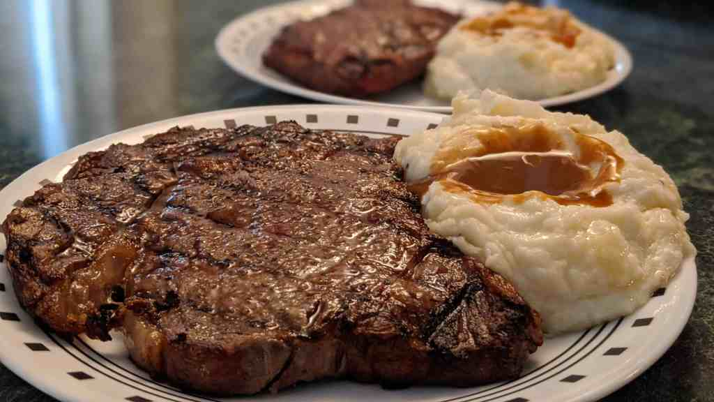 photo of a ribeye steak with mashed potatoes and gravy after grilling frozen steaks