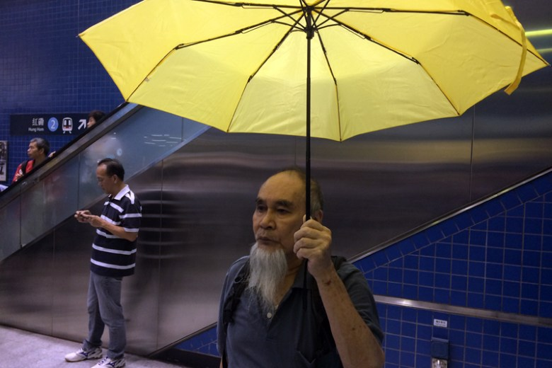 Mr Lee without musical instrument but yellow umbrella.