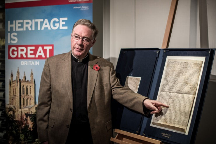 Hereford Cathedral's Chancellor Canon Chris Pullin points to a replica of a Magna Carta charter, considered to represent the foundation of rule of law in the West, during a preview ahead of its public exhibition in Hong Kong on November 10, 2015. Photo: AFP/ Philippe Lopez.