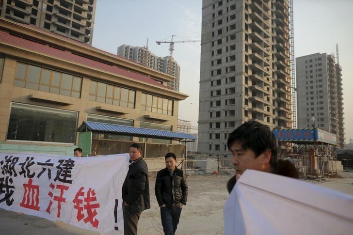 Migrant workers display banners. Photo: Damir Sagolj, Reuters.