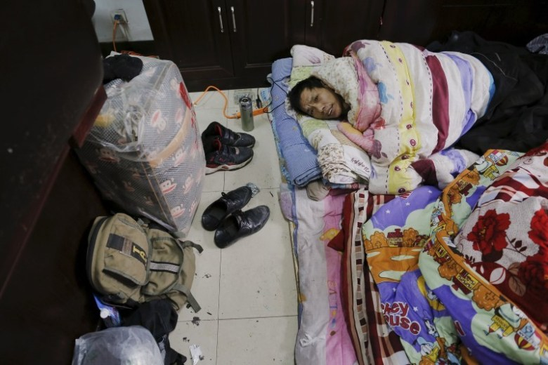 A migrant worker wakes up at the offices. Photo: Damir Sagolj, Reuters.