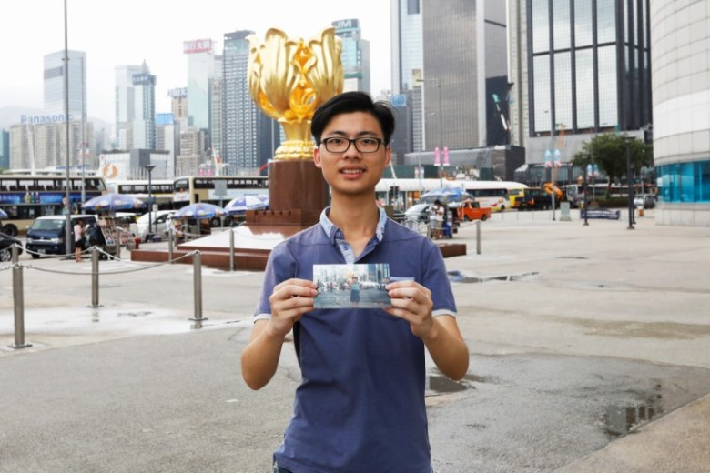 Kalok Leung poses with his childhood photo which was taken at the same spot in 2002, at Golden Bauhinia Square in Hong Kong