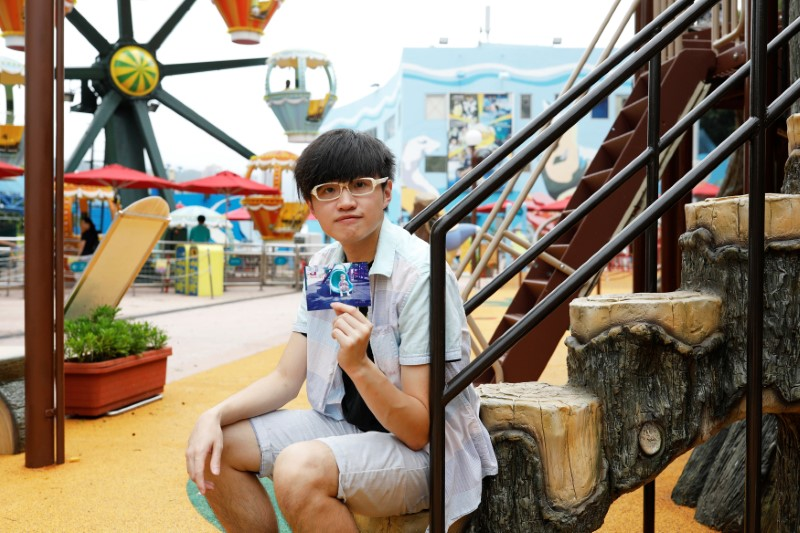 JoJo Wong poses with his childhood photo which was taken around the same spot in 1999, at Ocean Park in Hong Kong