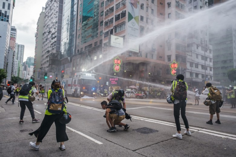 press reporters water cannon police protest