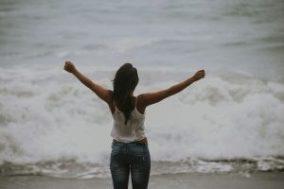 Eine Frau steht am Meer und will Loslassen