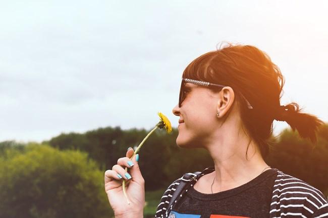 Eine Frau die an der Blume riecht und den Neuanfang genießt.