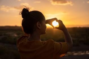 Eine Frau im Sonnenuntergang sagt Mantras zum Glück
