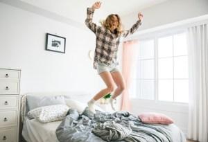Eine Frau springt am Bett, weil das glücklicher macht